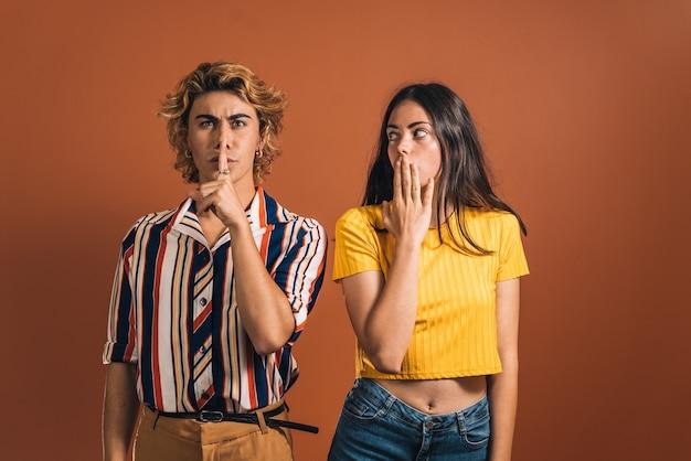 Elegancki kaukaski mężczyzna z gestem ciszy i zdziwioną młodą kobietą na brązowym tle. blondyn i brunetka