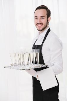 Elegancki kelner serwujący kieliszki do szampana