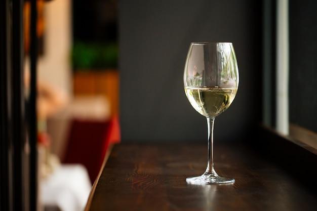 Elegancki kieliszek białego wina na drewnianym blacie barowym