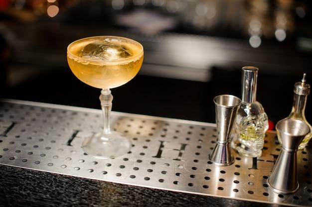 Elegancki kieliszek koktajlowy wypełniony napojem alkoholowym na blacie barowym