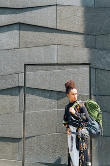 Elegancki kobiety przewożenia plecak patrzeje daleko od przy outdoors