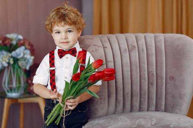 Elegancki ładny mały chłopiec z bukietem tulipanów