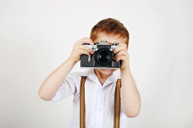 Elegancki mały fotograf z szelkami i analogową kamerą na kliszę
