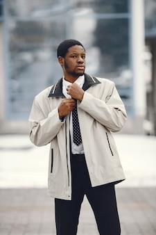 Elegancki mężczyzna afroamerykanin stojący na ulicy.