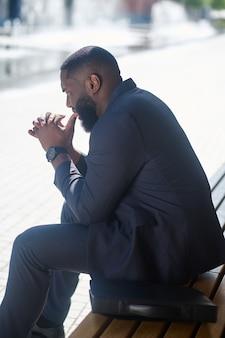Elegancki mężczyzna. afroamerykanin w eleganckim garniturze siedzący na ławce