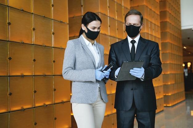 Elegancki mężczyzna i kobieta w gumowych rękawiczkach i maskach, stojąc w hotelowym holu ze swoimi gadżetami