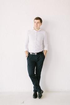 Elegancki mężczyzna patrzy w bok, stojąc w pobliżu białej tapety z rękami w kieszeniach