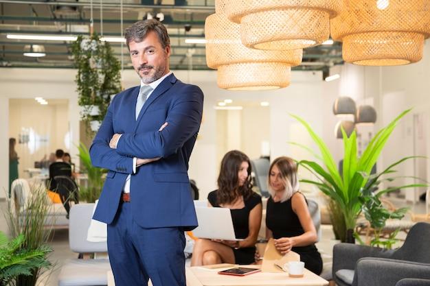 Elegancki mężczyzna pozuje w kostiumu przy biurem