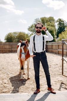 Elegancki mężczyzna stojący obok konia na ranczo