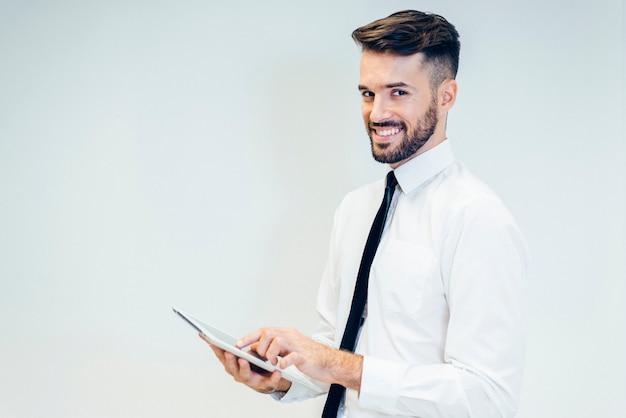 Elegancki mężczyzna uśmiecha się podczas oglądania tabletkę