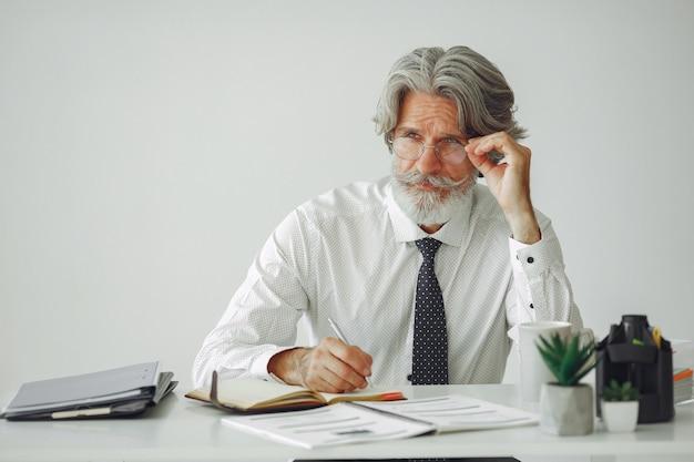 Elegancki mężczyzna w biurze. biznesmen w białej koszuli. mężczyzna pracuje z dokumentami.