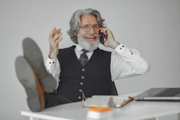 Elegancki mężczyzna w biurze. biznesmen w białej koszuli. mężczyzna pracuje z telefonem.