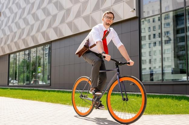 Elegancki mężczyzna w formalnej odzieży i okularach, patrząc do przodu, jadąc rowerem w środowisku miejskim na zewnątrz centrum biznesowego