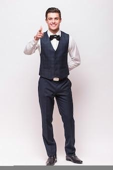 Elegancki mężczyzna w garniturze na białym tle na białej ścianie