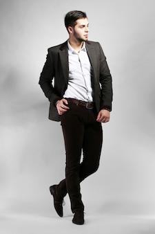Elegancki mężczyzna w garniturze na szarej ścianie
