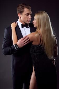 Elegancki mężczyzna w garniturze z muszką delikatnie obejmuje seksowną kobietę.