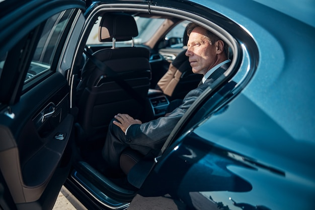 Elegancki mężczyzna w klasycznym garniturze podróżuje samochodem z kierowcą po przybyciu na lotnisko