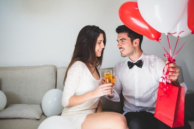 Elegancki mężczyzna z balonami i czerwona torba opiekania ze swoją dziewczyną