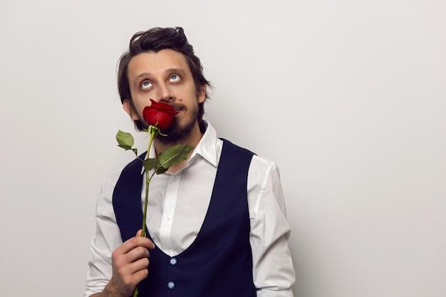Elegancki mężczyzna z brodą i okularami na walentynki w białej koszuli i kamizelce na białej ścianie stoi z czerwoną różą