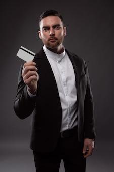 Elegancki mężczyzna z brodą trzyma kartę kredytową.