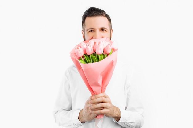 Elegancki mężczyzna z brodą z bukietem tulipanów, prezent na walentynki