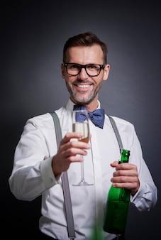 Elegancki mężczyzna z butelką szampana i fletem szampana