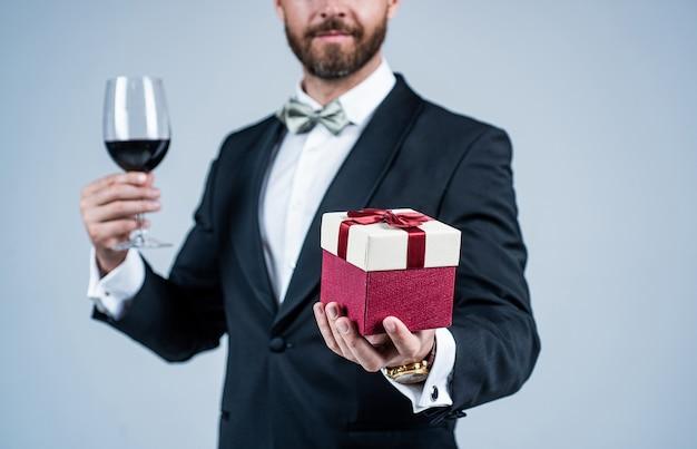 Elegancki mężczyzna z nieogoloną twarzą przycięty widok w świąteczny strój świąteczny trzymać kieliszek do wina czerwonego i pudełko szare tło, uroczystość.