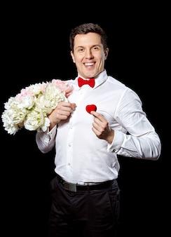 Elegancki mężczyzna z pierścieniem i kwiatami