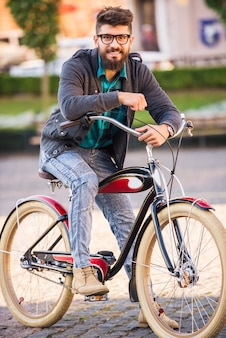 Elegancki mężczyzna z szkłami jedzie bicykl.