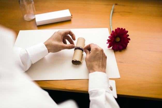 Elegancki mężczyzna zawiązuje rolkę papieru, wysyłając wiadomość do butelki.
