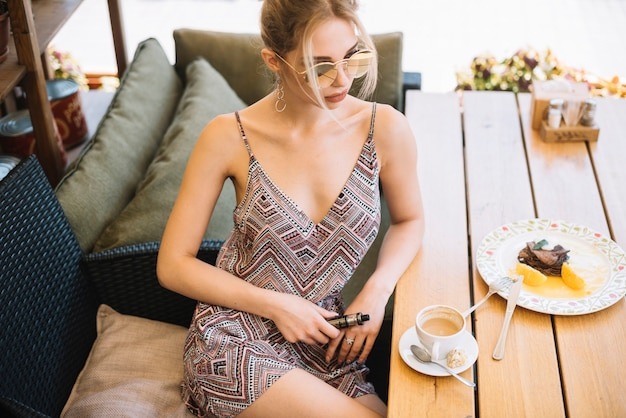 Elegancki młodej kobiety obsiadanie przy kawiarnią z kawą i śniadaniem