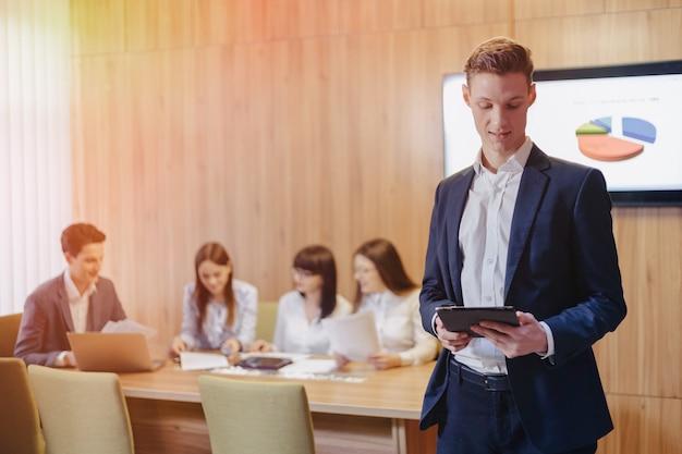 Elegancki młody biznesmen jest ubranym kurtkę i koszula na tle pracujący biuro z ludźmi pracuje z pastylką