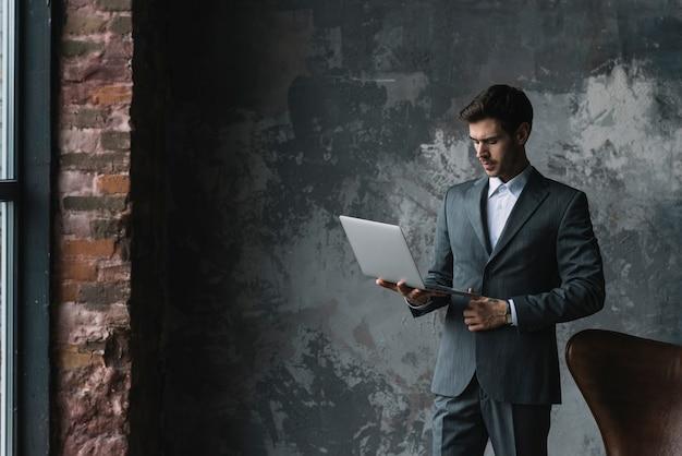 Elegancki młody biznesmen patrzeje laptop w jego ręce