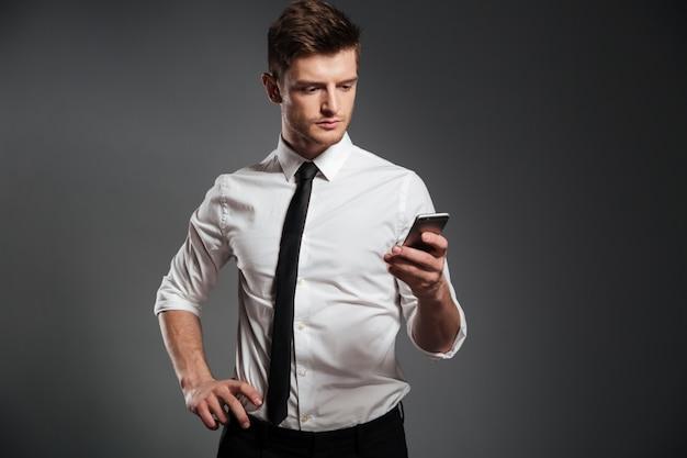 Elegancki młody biznesmen używa telefon komórkowego podczas gdy stojący