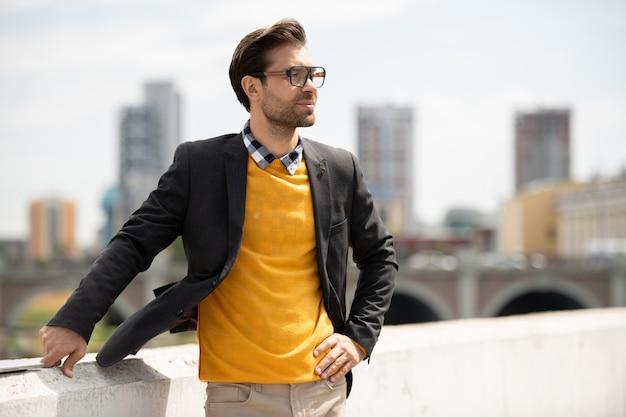 Elegancki młody biznesmen w kurtce, żółtym swetrze i dżinsach stojący nad brzegiem rzeki w środowisku miejskim