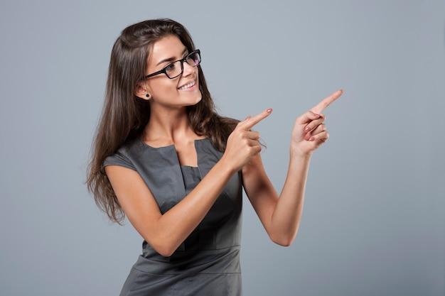 Elegancki młody bizneswoman wskazuje na boku