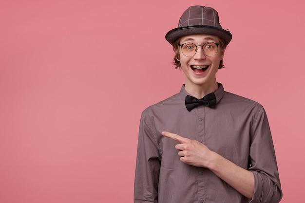 Elegancki młody chłopak otworzył usta z podniecenia, jest przytłoczony pozytywnymi emocjami radość szczęścia na różowym tle, wskazując palcem wskazującym w lewo na miejsce