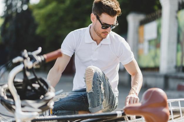 Elegancki młody człowiek naprawia bicykl na drodze