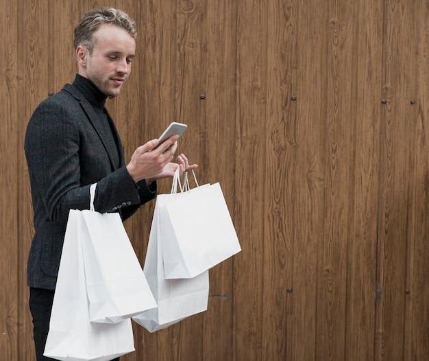 Elegancki młody człowiek patrzeje smartphone