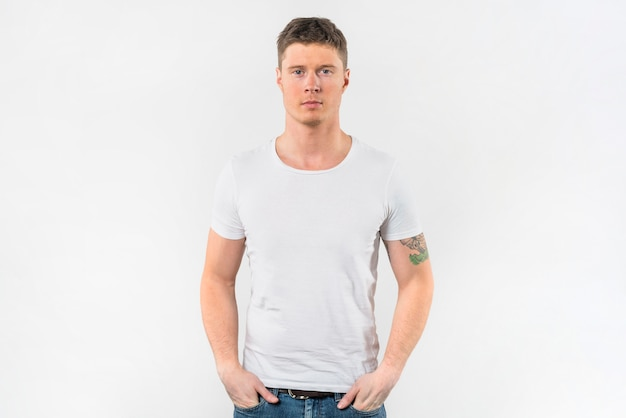 Elegancki młody człowiek z jego rękami w kieszeni przeciw białemu tłu