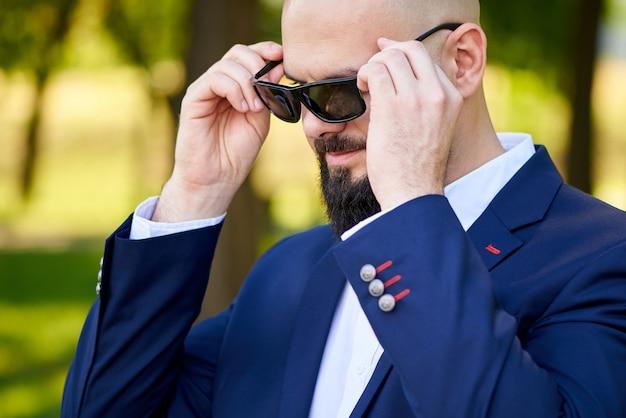 Elegancki młody człowiek z okularami przeciwsłonecznymi outdoors.