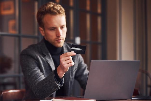 Elegancki młody facet w wizytowym siedzi w kawiarni z laptopem i kartą kredytową w ręku.