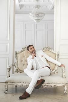 Elegancki młody przystojny mężczyzna z brodą w białym klasycznym garniturze. wnętrze hotelu. studio fotograficzne. sofa. okno. krzesło. żyrandol