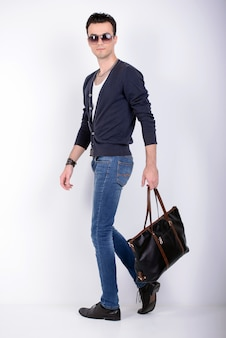 Elegancki młody przystojny mężczyzna z torbą.