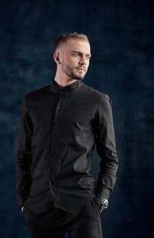 Elegancki młody przystojny nowoczesny mężczyzna. studio portretowe moda, moda, człowiek sukcesu. kopia przestrzeń, ciemne tło.
