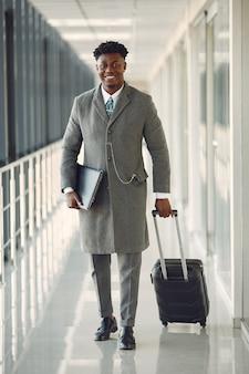 Elegancki murzyn na lotnisku z walizką