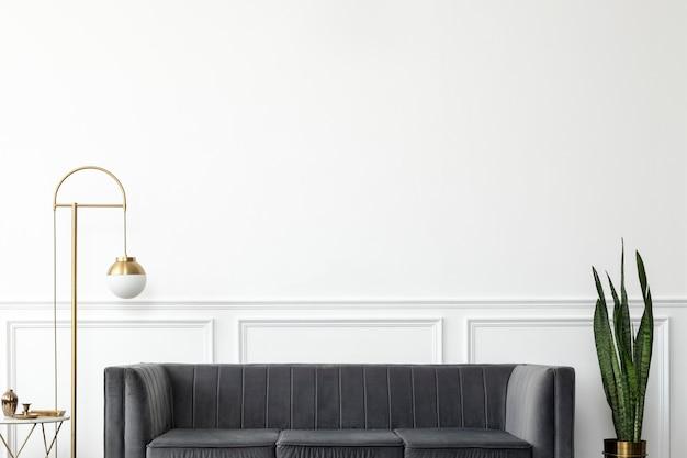 Elegancki, nowoczesny, luksusowy salon w stylu mid-century z szarą aksamitną kanapą i złotą lampą