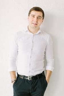 Elegancki pan młody w białej spódnicy stojący w pobliżu białej tapety z rękami w kieszeniach