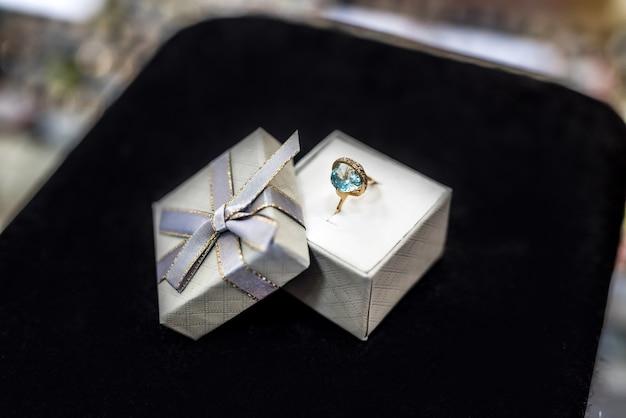 Elegancki pierścionek z topazem na czarnym tle