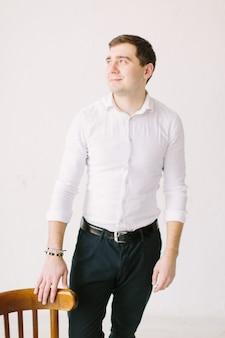 Elegancki, przystojny pan młody w białej spódnicy stojący w białym pokoju z drewnianym krzesłem